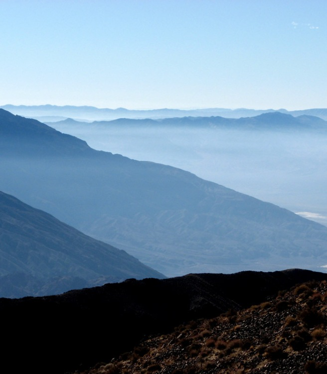 Rows of blue misty ridges hovering over Death Valley